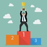 Uomo d'affari del vincitore con la conquista del supporto throphy su un podio Fotografia Stock