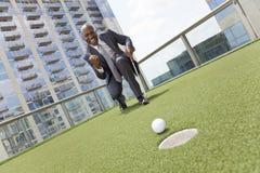 Uomo d'affari dell'afroamericano che gioca golf del tetto Immagini Stock