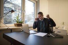 uomo d'affari dell'uomo d'affari che lavora al computer portatile in ufficio che prende le note che fanno telefonata soddisfatta  fotografie stock