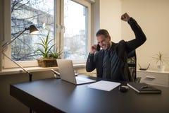 uomo d'affari dell'uomo d'affari che lavora al computer portatile in ufficio che prende le note che fanno telefonata soddisfatta  fotografia stock libera da diritti