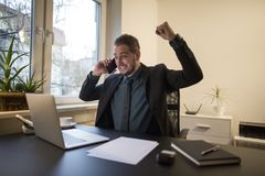 uomo d'affari dell'uomo d'affari che lavora al computer portatile in ufficio che prende le note che fanno telefonata soddisfatta  immagine stock libera da diritti