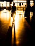 Uomo d'affari della siluetta in aeroporto che prepara per la partenza Immagini Stock Libere da Diritti