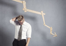 Uomo d'affari deludente davanti al grafico che indica giù. Immagine Stock