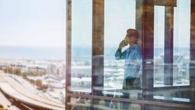 Uomo d'affari dentro l'edificio per uffici che parla sul telefono cellulare Fotografie Stock Libere da Diritti