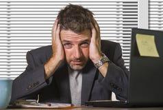 Uomo d'affari depresso e frustrato attraente che lavora allo scrittorio del computer di ufficio disperato ed enorme con l'affare  fotografia stock