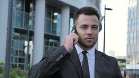 Uomo d'affari di camminata Talking sul telefono video d archivio