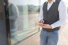 Uomo d'affari di camminata Using Tablet Outside immagini stock libere da diritti
