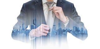 Uomo d'affari di doppia esposizione che lega cravatta e le costruzioni moderne nella città Immagine Stock