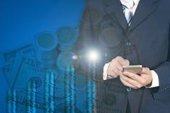 Uomo d'affari di doppia esposizione facendo uso dello Smart Phone sulla pila di monete Fotografia Stock