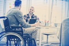 Uomo d'affari di handicap che discute con il collega nell'ufficio fotografie stock