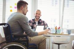 Uomo d'affari di handicap che si siede con il collega in ufficio immagine stock libera da diritti
