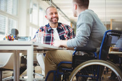 Uomo d'affari di handicap che si siede con il collega in ufficio fotografia stock libera da diritti