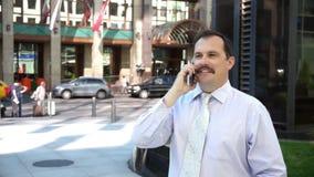 Uomo d'affari di medio evo che parla facendo uso dello smartphone archivi video