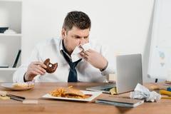uomo d'affari di peso eccessivo che mangia le guarnizioni di gomma piuma, hamburger e le patate fritte mentre lavorando con il co immagini stock libere da diritti