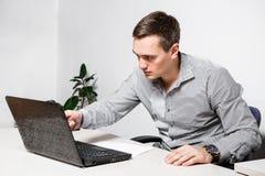Uomo d'affari di preoccupazione che utilizza computer portatile mentre sedendosi nell'ufficio Indica una penna sullo schermo, leg fotografia stock libera da diritti