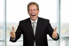Uomo d'affari di risata che gesturing i pollici su immagine stock