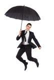 Uomo d'affari di salto con un ombrello Fotografie Stock Libere da Diritti