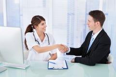 Uomo d'affari di saluto di medico in clinica Fotografia Stock Libera da Diritti