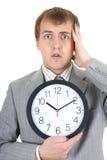 Uomo d'affari di Shoked che tiene un orologio Fotografia Stock