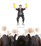 Uomo d'affari di successo facendo uso del megafono di acclamazione che celebra con il gruppo Immagine Stock