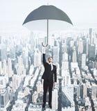 Uomo d'affari di volo con l'ombrello al fondo della città di megapolis Fotografia Stock Libera da Diritti