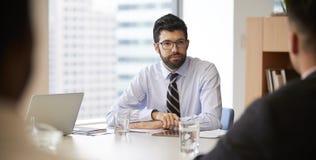 Uomo d'affari With Digital Tablet che si siede alla riunione della Tabella con i colleghi in ufficio moderno immagine stock libera da diritti