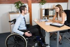 Uomo d'affari disabile bello in una sedia a rotelle al suo ufficio davanti ad una bella giovane donna immagine stock