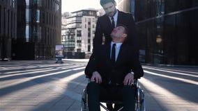Uomo d'affari disabile che cammina con il suo amico all'aperto stock footage
