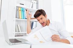 Uomo d'affari disperato arrabbiato che si siede alla tavola e che tiene i documenti Fotografie Stock Libere da Diritti