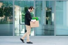 Uomo d'affari disperato ed infornato che cammina a partire dall'ufficio Fotografie Stock Libere da Diritti