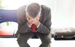 Uomo d'affari disperato nella sala di attesa fotografia stock