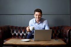 Uomo d'affari Drinking Coffee Whilst che lavora al computer portatile in Internet fotografia stock libera da diritti