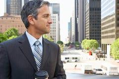 Uomo d'affari Drinking Takeaway Coffee fuori dell'ufficio Fotografia Stock