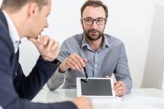 Uomo d'affari due che per mezzo del dispositivo della compressa dello schermo in bianco mentre sedendosi allo scrittorio su una r immagini stock libere da diritti