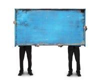 Uomo d'affari due che tiene vecchio tabellone per le affissioni di legno in bianco blu Fotografie Stock