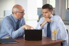 Uomo d'affari due con il computer portatile, ufficio come priorità bassa Fotografia Stock Libera da Diritti