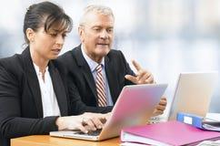 Uomo d'affari e donna che lavorano ad un computer portatile Fotografie Stock Libere da Diritti