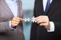 Uomo d'affari e donna di affari con i pezzi di puzzle Immagini Stock