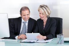 Uomo d'affari e donna di affari maturi sul lavoro Fotografie Stock