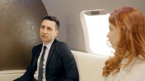 Uomo d'affari e donna di affari che discutono i loro piani che volano in aereo privato video d archivio