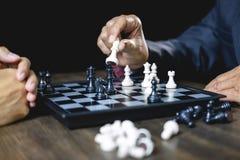 Uomo d'affari e donna di affari che giocano scacchi e che pensano il rovesciamento di arresto di strategia all'analisi opposta di fotografia stock libera da diritti