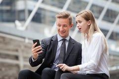 Uomo d'affari e donna di affari che utilizza insieme smartphone nella città all'aperto Colleghi eccitati con il telefono cellular fotografie stock libere da diritti