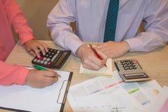 Uomo d'affari e lavorare femminile alla scrivania con il calcolatore, una penna ed il documento Fotografia Stock Libera da Diritti
