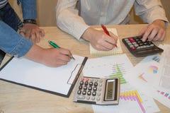 Uomo d'affari e lavorare femminile alla scrivania con il calcolatore, una penna ed il documento Fotografia Stock