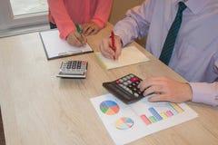 Uomo d'affari e lavorare femminile alla scrivania con il calcolatore, una penna ed il documento Immagini Stock