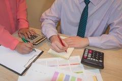 Uomo d'affari e lavorare femminile alla scrivania con il calcolatore, una penna ed il documento Immagini Stock Libere da Diritti