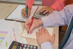 Uomo d'affari e penna a sfera femminile della tenuta della mano che lavorano al calcolatore, concetto online di lavoro Immagine Stock