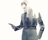 Uomo d'affari e una città facendo uso di una compressa immagine stock