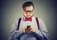 Uomo d'affari eccentrico della barba con nei vetri facendo uso di uno smartphone immagine stock libera da diritti