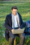 Uomo d'affari elegante bello che lavora in un parco Fotografia Stock